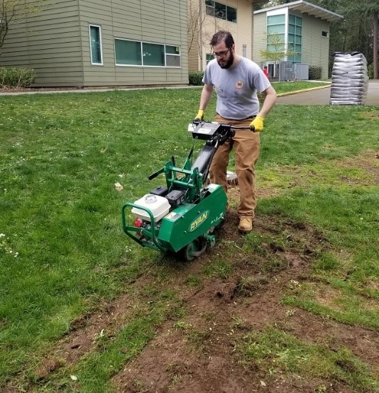 Care Force member using sod cutter on a large grassy area with a building in the background.