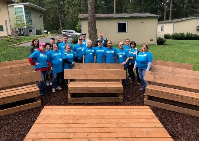 A group of AT&T volunteers wearing blue t-shirts stand around benches with backs and a stage.