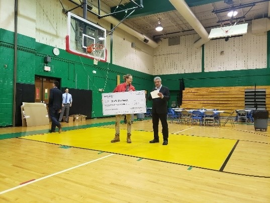 Senior AmeriCorps Member Clark Shimeall stands holding a large check in his iconic red jacket next to a Taco Bell representative after receiving the Taco Bell Live Más Scholarship.