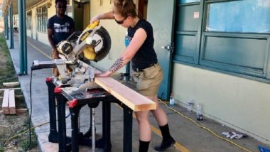 Two AmeriCorps Members use a chop saw on a saw horse to cut wood.