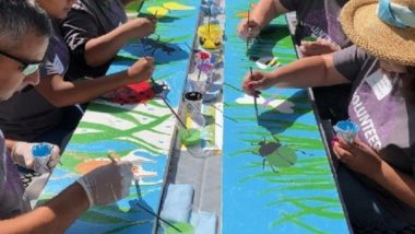 Volunteers sit at a picnic table painting bugs and grass onto bench backs.