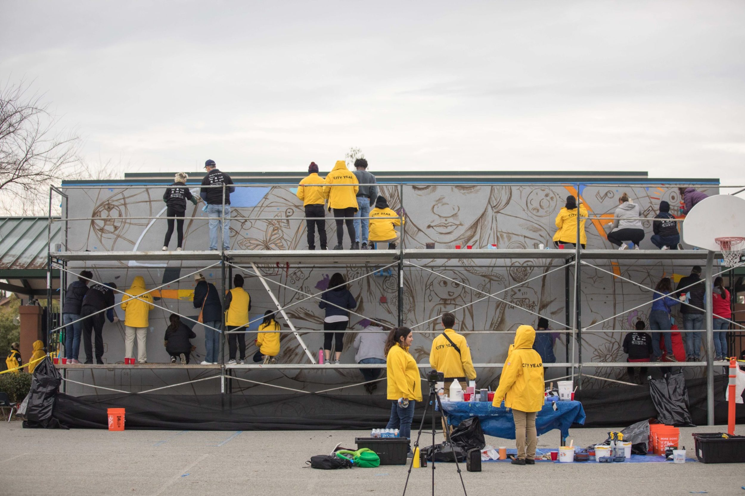 City Year AmeriCorps members and community volunteers paint a large mural at San Antonio Elementary School for MLK Day of Service
