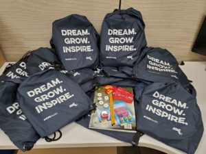 Black drawstring bags with the words, Dream, Grow, Inspire on them. Also included are the items that fill these bags: a spiral notebook, pencils, erasers, pencil sharpener, candy, and mints.