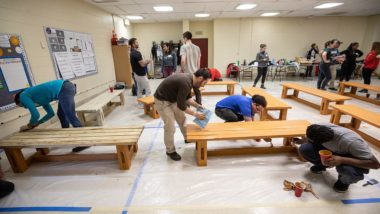 Volunteers stain backless benches on tarp covered floor.