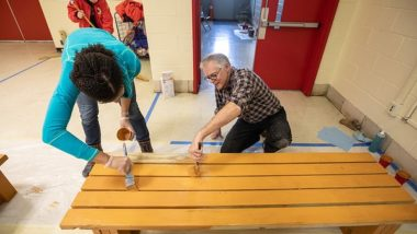 Volunteers stain a backless bench during MLK Day of Service.