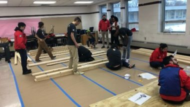 Volunteers stand in a room with piles of lumber for a construction project.