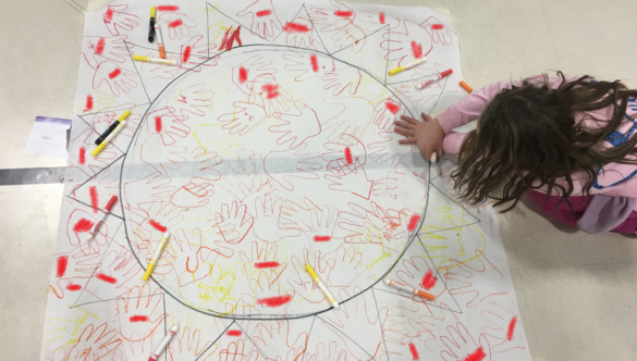 Students add their handprints to the sun at McDonough's literacy night