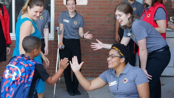 City Year corps members greet students on the first day of school