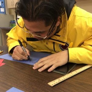 A city year americorps member colors on a piece of construction paper