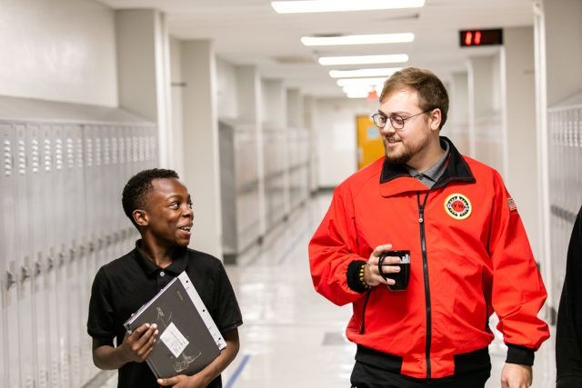 City Year AmeriCorps member with student at school