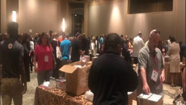 Aramark volunteers stand in a ballroom at various tables packing boxes.