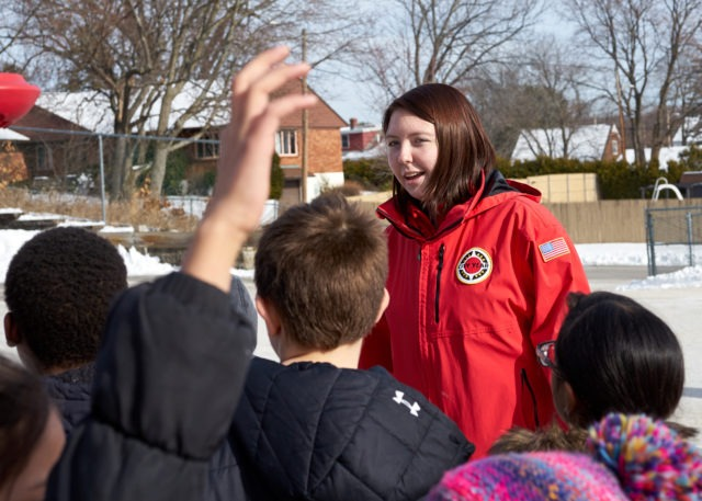 A corps member runs games during recess to help kids cooperate and have fun