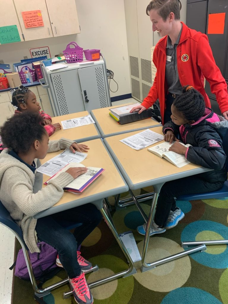 AmeriCorps member in red jacket mentors students with books open in Jacksonville, Florida.