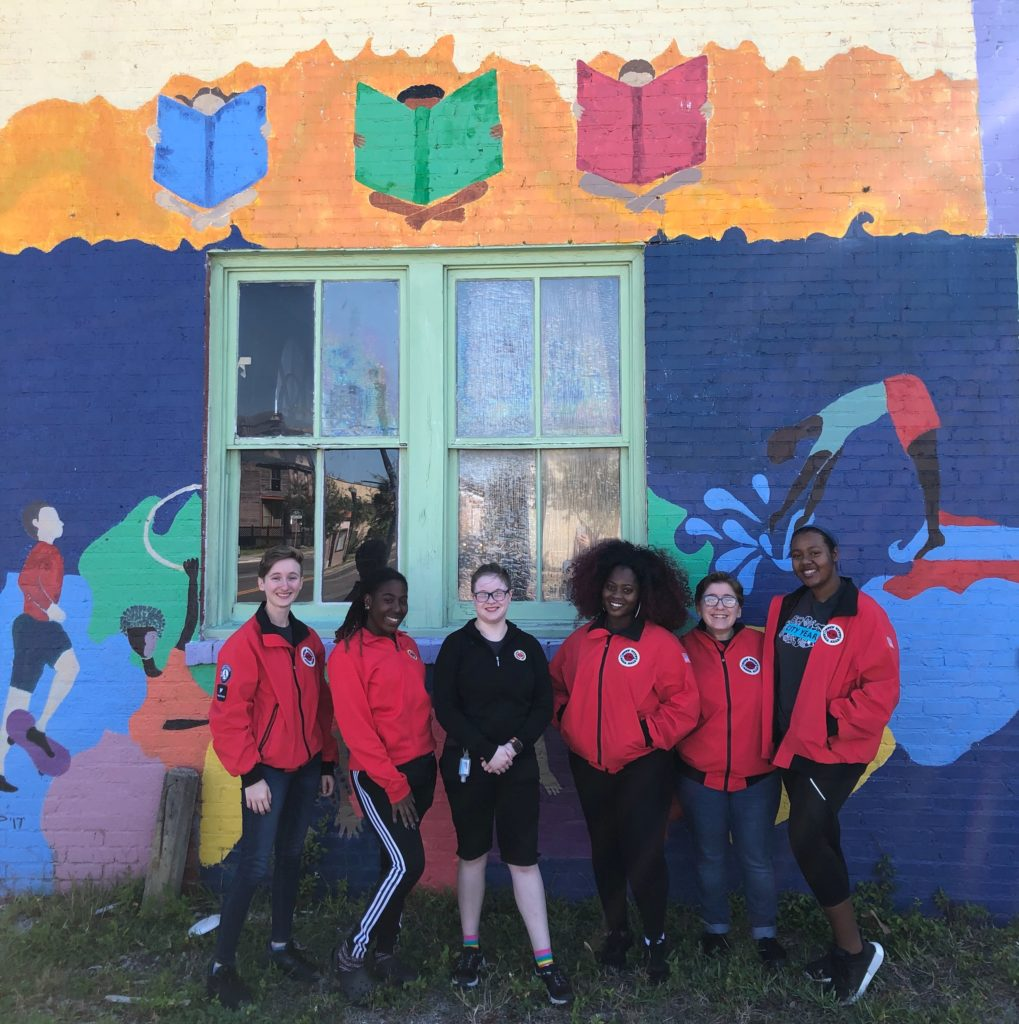 AmeriCorps members stand in front of a colorful mural with their red jackets on.
