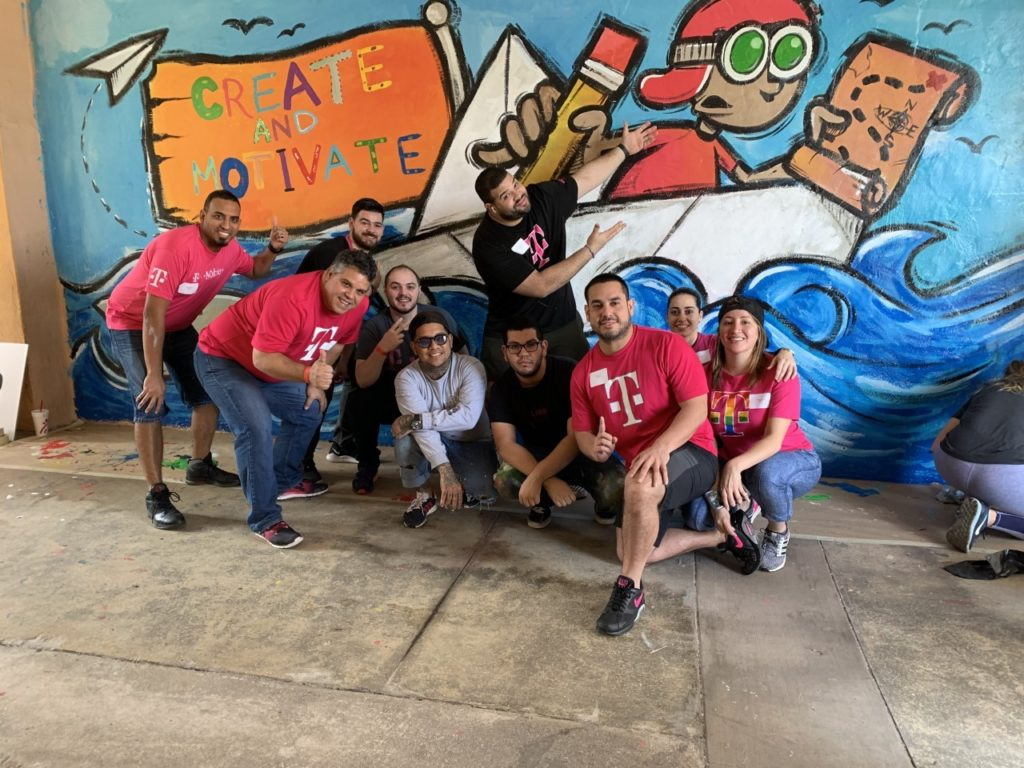 T-Mobile volunteers pose in front of mural of a young boy in a boat with a pancil and map in hand. His flag has the phrase Create and Motivate written on it in different colors.