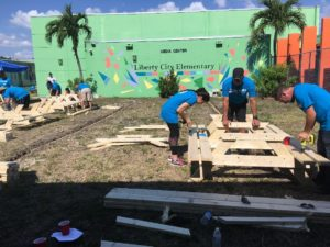 Volunteers in blue shirts build adult picnic tables on the lawn of Liberty City Elementary School.