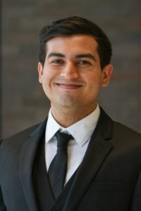 Headshot of Care Force alumni Alejandro wearing a black suit and tie standing in front of a gray background.