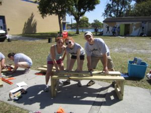 Three volunteers pose with backless bench they are building.