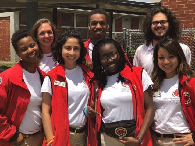 A group of smiling AmeriCorps members pose for a photo at a Duval County Public School.