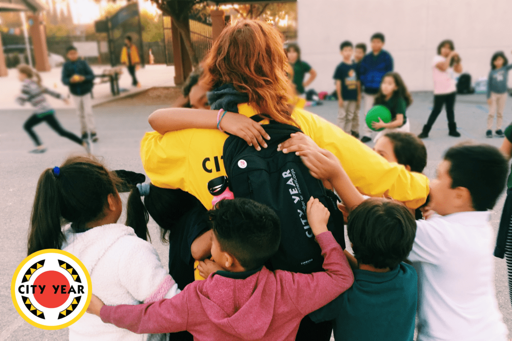 Maraina Weyl, a City Year San José AmeriCorps member, in a yellow jacket being surrounded by students at her school who are hugging her.