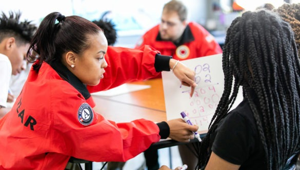 City Year AmeriCorps in school service red uniform