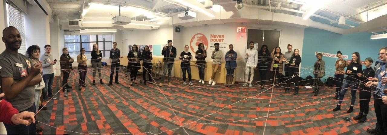 Civic Engagement members stand in a circle and hold string that forms a twisted web to illustrate the connections formed.