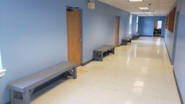 Hallway with blue walls and backless benches in the spaces between classrooms.