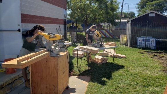 Two Care Force AmeriCorps Members cut wood using chop saws.