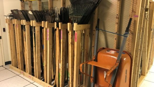 Various landscaping tools in a wooden storage rack. An orange wheelbarrow leans against the wall beside it.