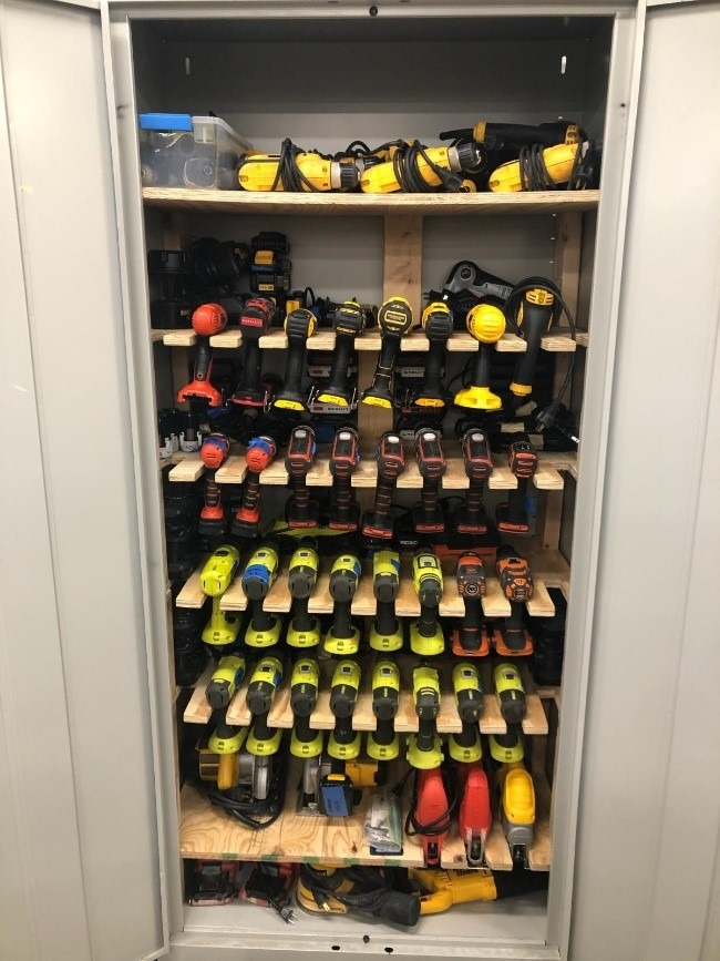 Open cabinet showing custom shelves for drills storage.