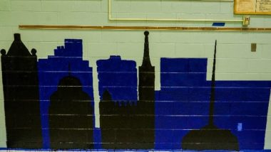 Mural of the Milwaukee skyline painted in blue and black.