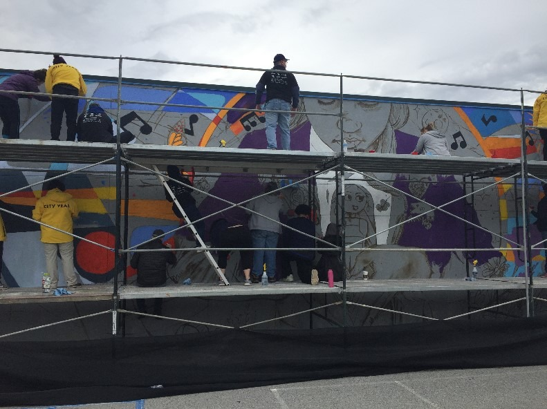 Two individuals in yellow City Year jackets and one individual in a black jacket stand on scaffolding as they work on a large mural.