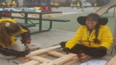Two women in yellow jackets work on a construction project.