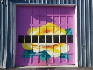 A garage door painted with a flower is shown.