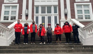 The City Year tam at ARISE Academy stands on the front steps of the school in their striking City Year red jackets