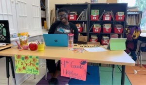 A City Year AmeriCorps members sits at her command center to support distance learning, bringing joy and enthusiasm