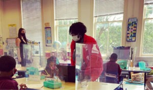 AmeriCorps member supports in a classroom with students with masks and dividers