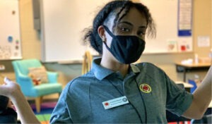 A City Year AmeriCorps member gestures to her empty middle school classroom proudly