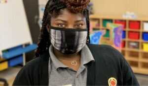 A City Year AmeriCorps member in a mask welcomes you to her elementary classroom