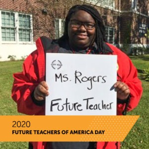 A City Year AmeriCorps member holds a board with her name Ms. Rogers and the title Future Teacher as she stands on the front lawn of her school. There is a banner that reads 2020 Future Teachers of America Day.