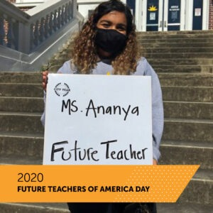 A City Year AmeriCorps member holds a board with her name Ms. Ananya and the title Future Teacher as she stands on the front steps of her school. There is a banner that reads 2020 Future Teachers of America Day.