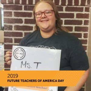 A City Year AmeriCorps member holds a board with her name Ms. T. There is a banner that reads 2019 Future Teachers of America Day.