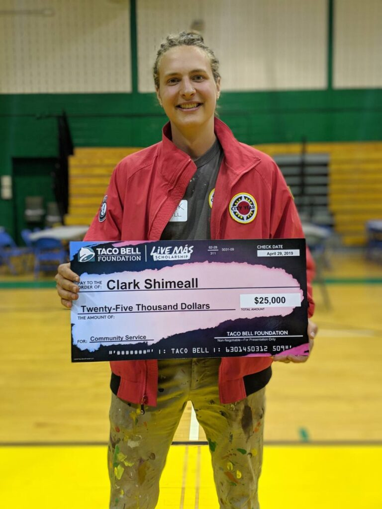Clark holds his scholarship check from the Taco Bell Foundation.