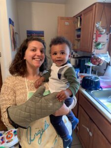 Angela, wearing an oven mitt, holds her baby, who is wearing an apron.