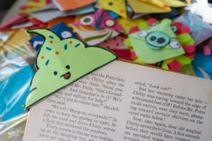 a bookmark shaped like a green ice cream cone holds open a copy of Chitty-Chitty-Bang-Bang. Other colorful bookmarks are spread out in the backround