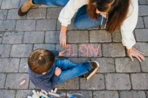 An aerial view of Amanda and her child writing on the sidewalk with chalk.