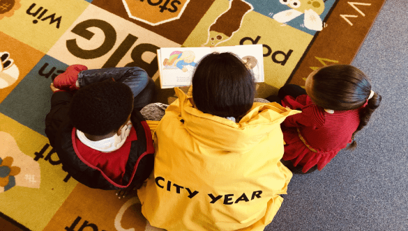 City Year in school service reading with students