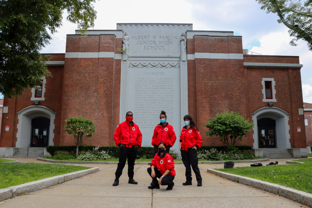 AmeriCorps members in their red City Year jackets gather in front of Albert Parlin School