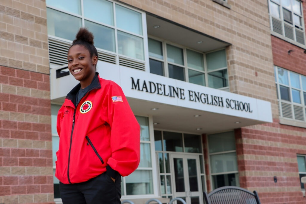 AmeriCorps member in red jacket, smiling in front of Madeline English School