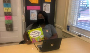 AmeriCorps member Samantha Richard poses in the classroom with a book she plans to read to her first grade students.